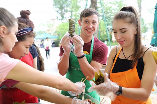 外国友人与大批游客在广东佛山学包粽子 感受中国端午节文化魅力